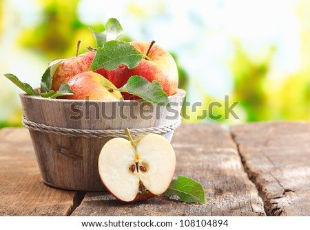 Wooden tub full of freshly harvested red apples with a halved apple on display on a wooden tabletop outdoors with copyspace - stock photo
