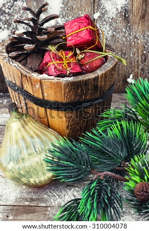 wooden tub with pine cones and Christmas decorations and ornaments.Selective focus - stock photo