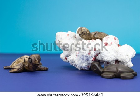 Wooden turtle figurines with coral on blue background - stock photo