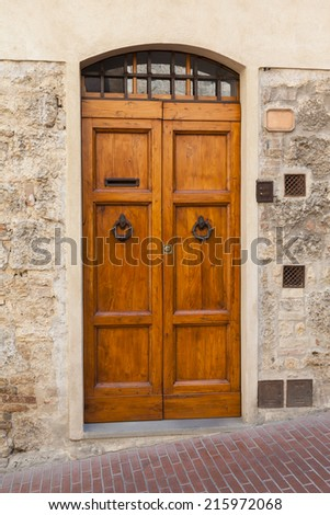 Wooden, Tuscan door in Italy - stock photo