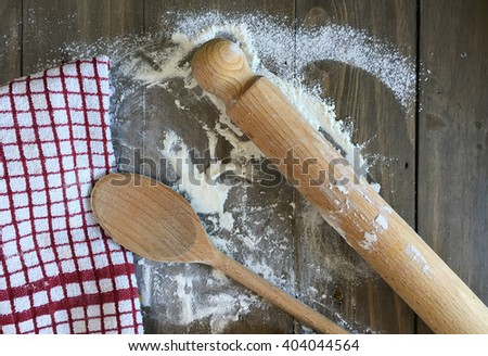 Wooden utensils and a tea towel on a flour covered wooden surface