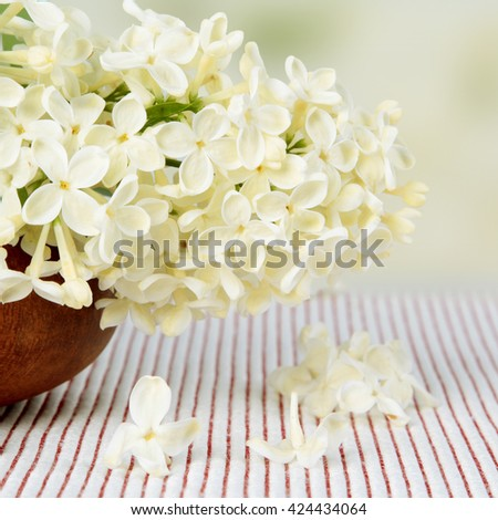 Wooden vase with a bouquet of white lilac spring flowers on textured background - stock photo