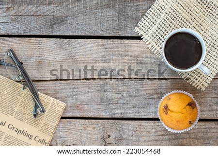 Wooden vintage background. Vintage newspaper and glasses, coffee cup and muffin on old wooden table  - stock photo