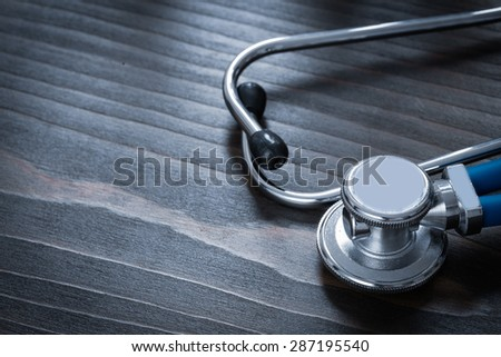 Wooden vintage board with blue medical stethoscope copy space image medicine concept  - stock photo