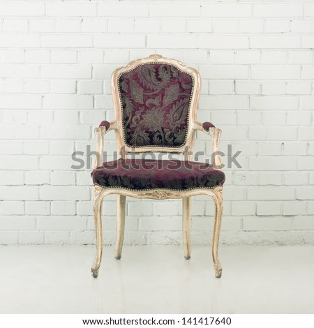 Wooden vintage chair against a brick wall