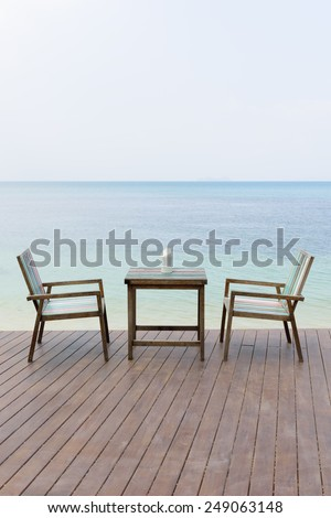 Wooden vintage table set with blue sky and sea background - stock photo