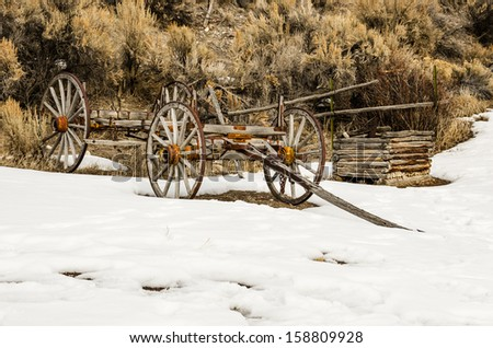 Wooden wagon frame with rusty wheel rims in the winter at Bannack State Park - stock photo