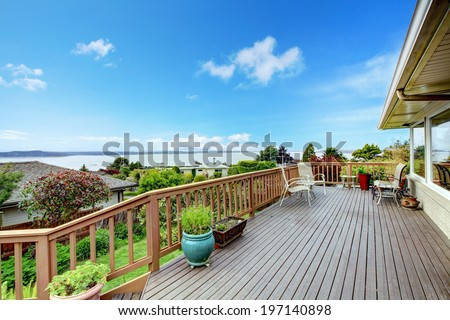Wooden walkout deck with patio table and water view. - stock photo