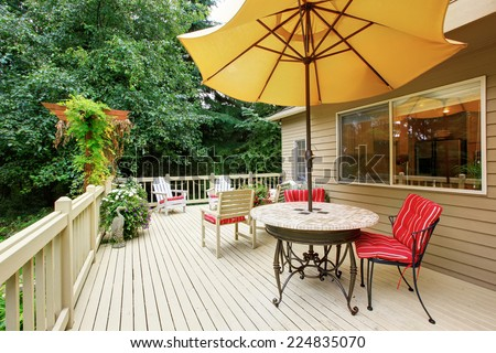 Wooden walkout deck with patio table, umbrella and chairs - stock photo