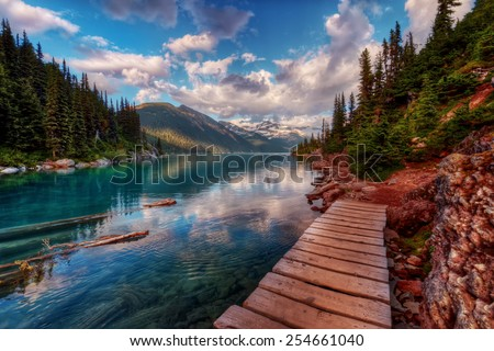 Wooden walkway along clear mountain lake and evergreen trees - stock photo
