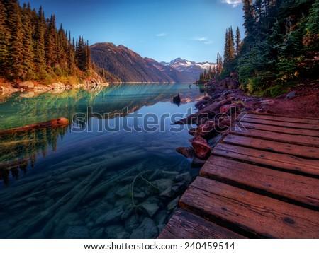 Wooden walkway along scenic mountain lake - stock photo