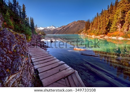 Wooden walkway along the glacial lake, with pine trees and mountains - stock photo