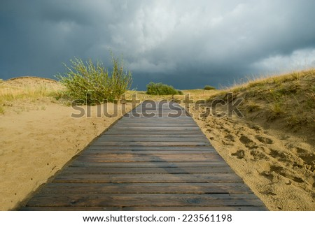 Wooden walkway leading to the beach over sand dunes - stock photo