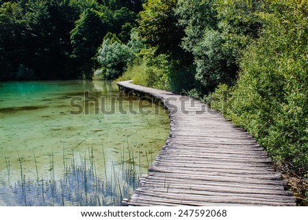 wooden walkway surrounded with crystal clear water and trees in National Park Plitvice Lakes in Croatia - stock photo