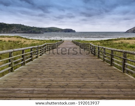 Wooden walkway to the sea with a cloudy sky