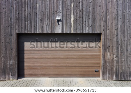 Wooden wall of modern rural garage with the automatic lifted gate. The motion sensor and the alarm system on a wall over an entrance