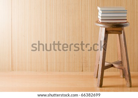 Wooden wall with old chair and books