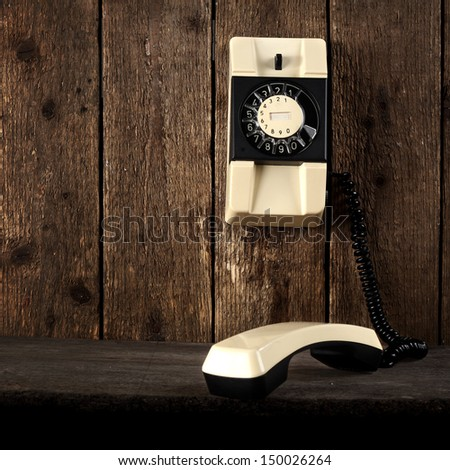 wooden wall with retro old telephone  - stock photo
