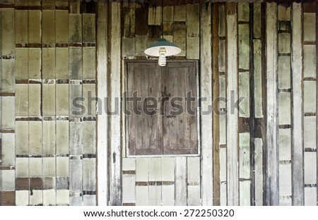 Wooden wall with window and lamp - stock photo