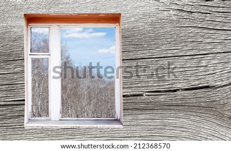 wooden wall with window outside forest clouds - stock photo