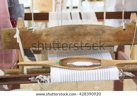 Wooden weaving shuttle  and Spool on an old manual weaving machine, Sackcloth thread in Loom - stock photo