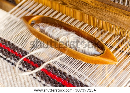 Wooden weaving shuttle on an old manual weaving machine - stock photo