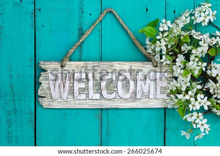 Wooden welcome sign with spring tree blossoms border hanging on antique teal blue wood background - stock photo