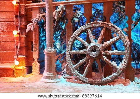 Wooden wheel in snow stand near beautiful railing; Spruce in snow behind railing - stock photo