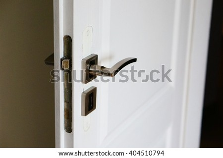 Wooden white open door with metal handle