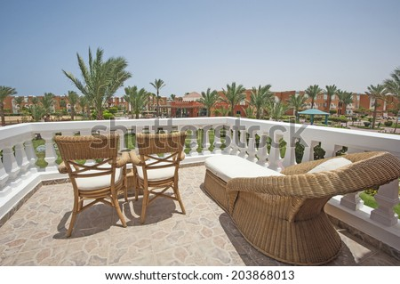 Wooden wicker chairs and sunbed on luxury tropical hotel balcony