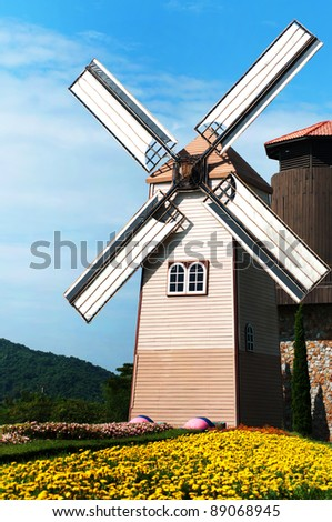 Wooden windmill on blue sky background - stock photo