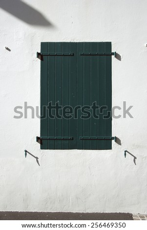 Wooden window shutters - Closed green shuttered wooden window in the Basque Country, France. - stock photo