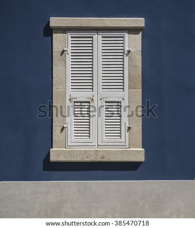 Wooden window shutters - Closed old shuttered weathered wooden window in the Limassol, Cyprus - stock photo