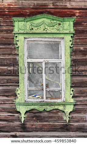 Wooden windows lacy architecture of old wooden houses in Tomsk, Siberia. Carved decoration salad color, white frame.