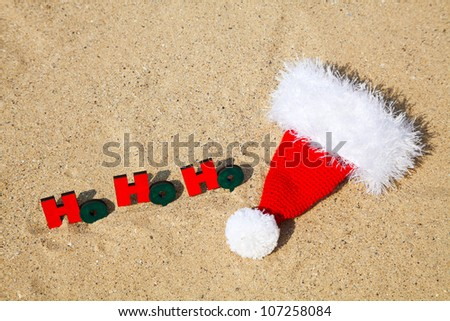 Wooden word 'Ho! Ho! Ho!' with Santa's hat on the sand