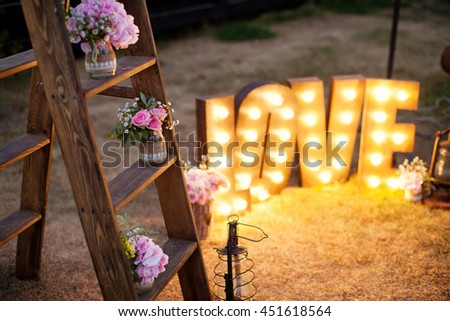 wooden word love with light bulbs and bouquets