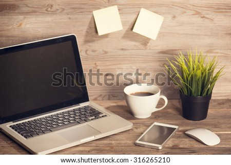 Wooden working desk with laptop, cup of hot coffee, mouse, smartphone and pot plant. Soft focus with noise in vintage toned. - stock photo