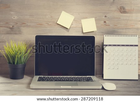 Wooden working table with laptop and calendar, in vintage tone. - stock photo