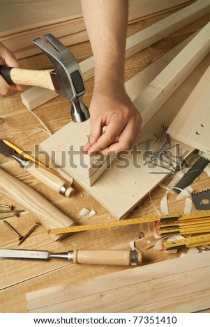 Wooden workshop table with tools. Man's arms hammering a nail
