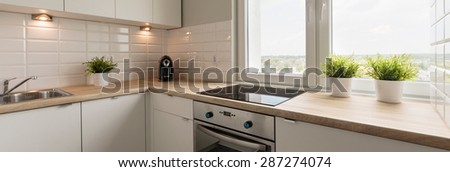 Wooden worktops and white cupboards in cozy kitchen - stock photo