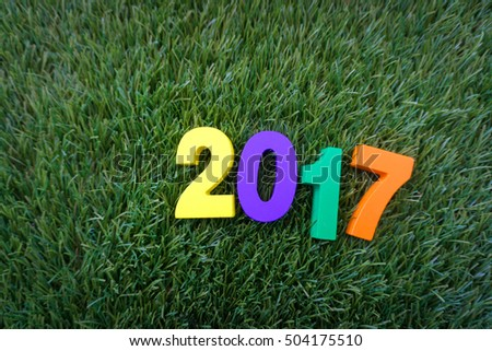 Wooden yellow, violet, green and orange on green grass - Concept number of Happy New Year 2017.