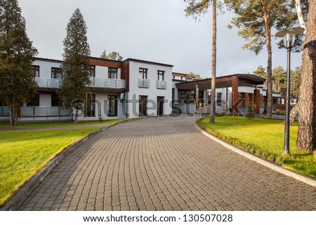 Woodland hotel - Cobbled road for modern hotel - stock photo