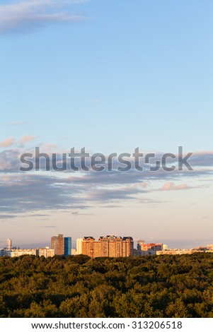 woods and apartment buildings under blue sky in summer evening - stock photo