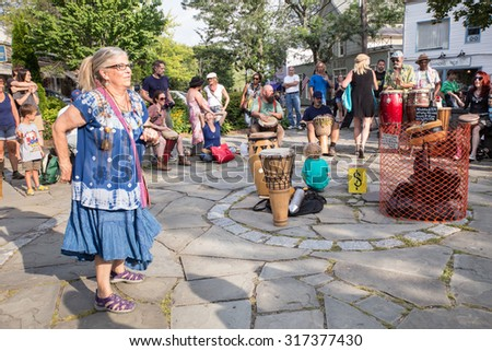 WOODSTOCK, NY - AUGUST 30, 2015:  Scene of drum circle gathering with people dancing in town square in Woodstock NY.   - stock photo