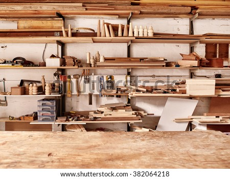 Woodwork workshop wall with many shelves holding a variety of wooden pieces and planks of wood, and some hand tools, with a wooden work bench in the foreground - stock photo