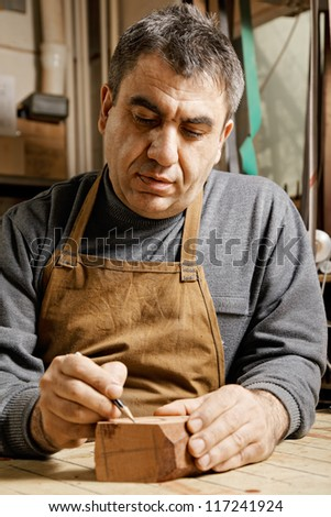 Woodworker in workshop drawing pipe on wood billet - stock photo