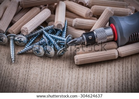 Woodworking dowels metal construction nails insulated screwdriver on wood board.