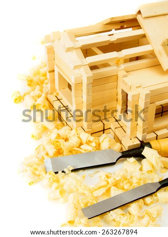 Woodworking. House construction. Joiner's works. The wooden house, chisel and shaving on white background. - stock photo