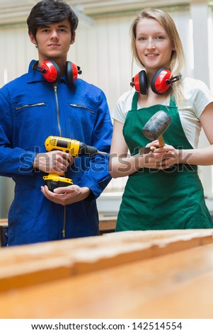 Woodworking students standing before a workbench and holding a driller and a hammer - stock photo