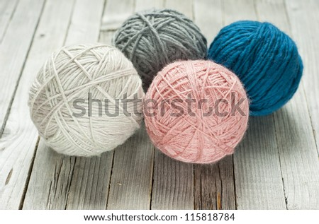 wool ball of threads on wooden table - stock photo